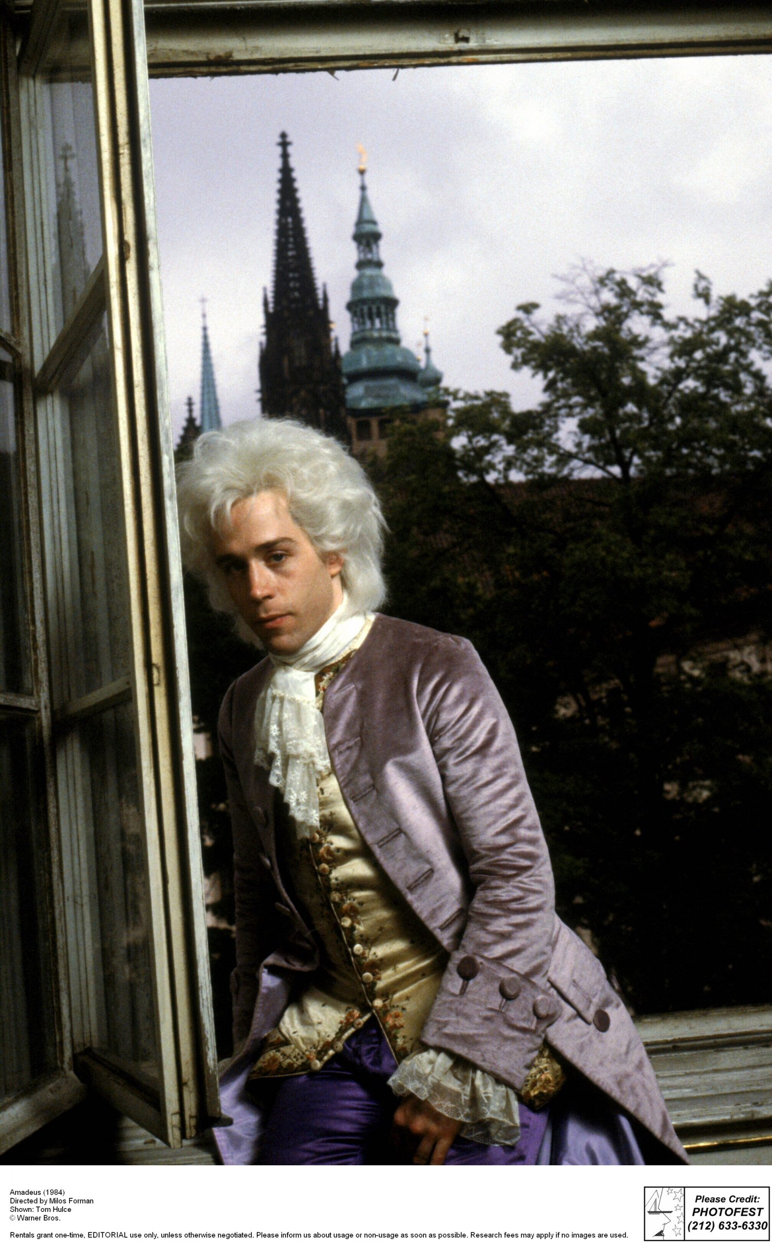 Man dressed as Mozart sitting on window sill with castle in background