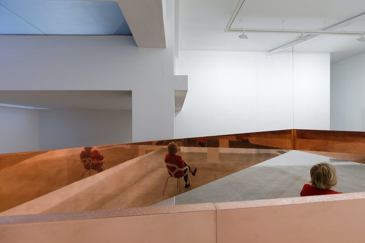 A woman in a red sweater sits inside a copper triangle suspended from the ceiling. She s reflected in the polished metal.