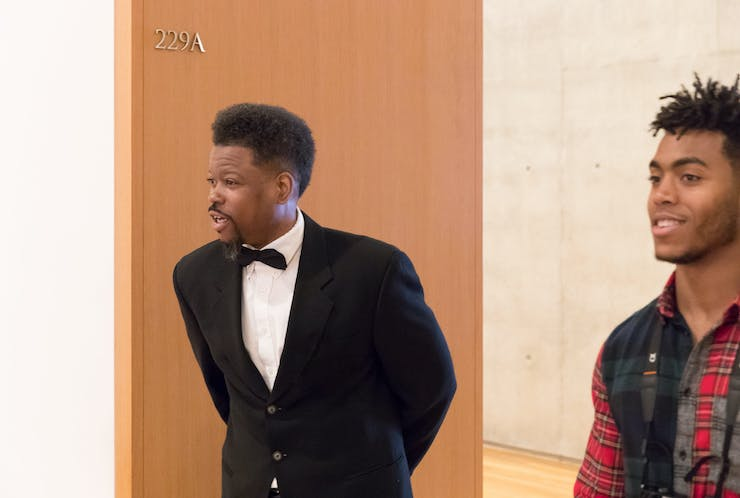 An African American man wearing a tuxedo stands at the entrance to a gallery. In the foreground, another man wearing a plaid shirt is smiling.