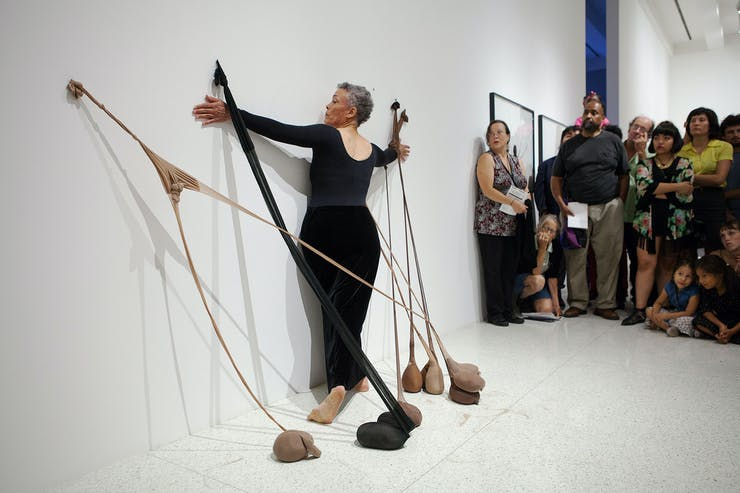 A black woman wearing tight black clothes dances between stretched pantyhose filled with sand attached to the gallery wall. There are audience members sitting and standing around her.