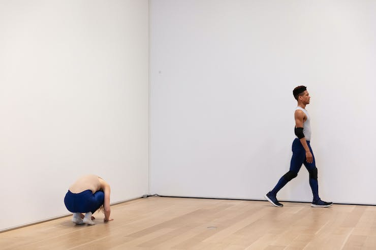 Two dancers wearing athletic clothes are in a white gallery. On the left, the female dancer is crouched low. On the right, a male dancer is walking to the right.