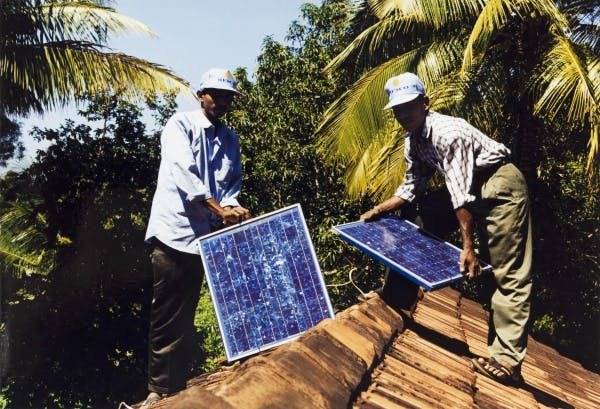Solar panels being installed by SELCO technicians for a rural house in Sri Lanka, 1994