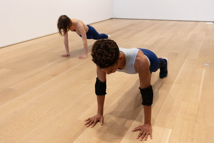 Two performers in a white gallery hold a plank position.