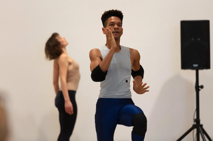 Two dancers in a white gallery. In the foreground, a male dancer in a gray tank top and elbow pads is running in place. In the background, a female dancer stands with her upper back arched. On the right side of the frame, there is a single speaker on a stand.