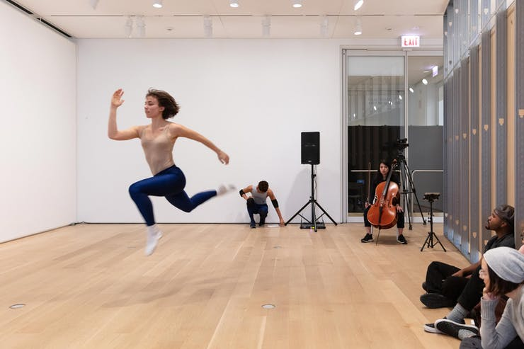 In a white box gallery, a dancer is seen jumping in mid air. A cellist plays in the background. Several audience members are seated on the floor.
