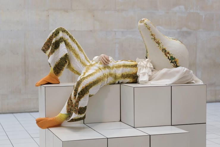 Performers wearing a striped jumpsuit and white squash mask lounges on a tiled pedestal.