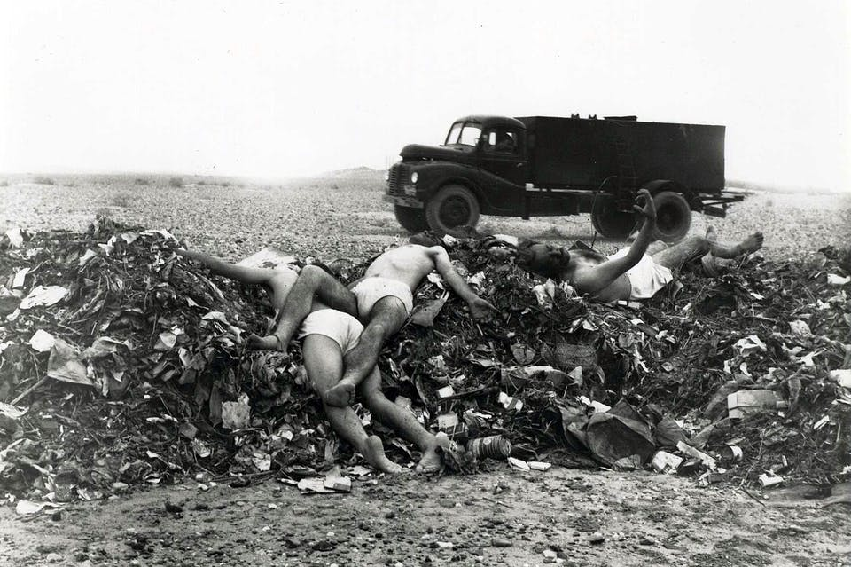 3 men, apparently dead, laying on top of a pile of garbage wearing only underwear. Truck in background.