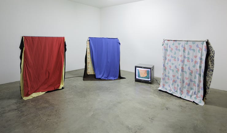 Three frames with cloths draped over them are arranged free standing in a gallery space with a television monitor in between them.