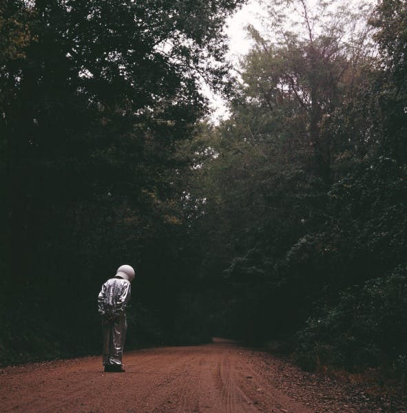 Man in space suit on a dirt road in woods.