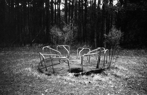 Black and white image of a playground ride for Come Home Charley Patton