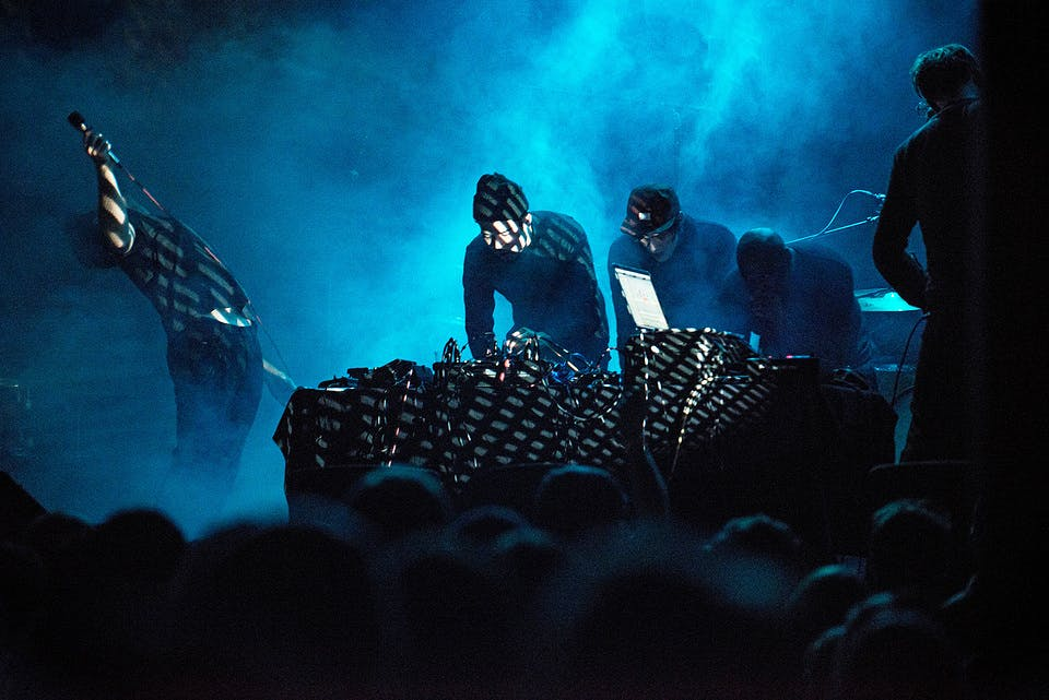 Blue/black image of a concert scene.