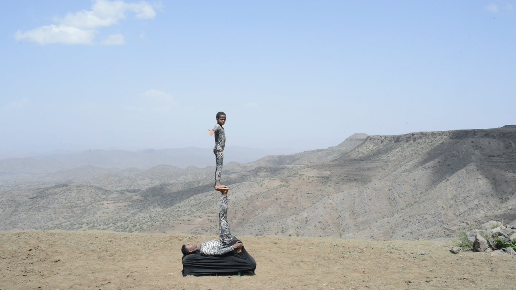 Image of one boy standing on another in the desert