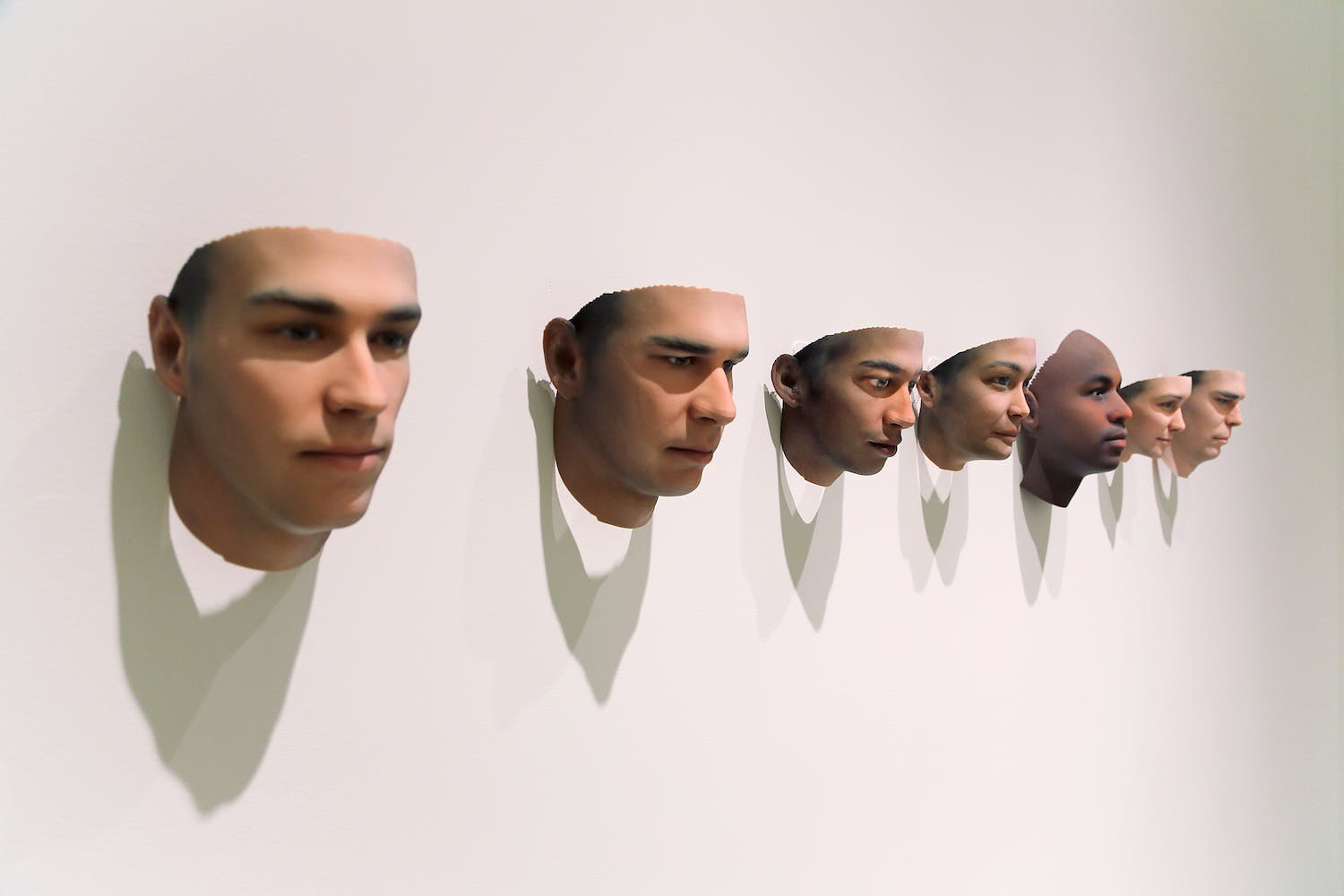 Seven 3d printed human heads mounted to a wall