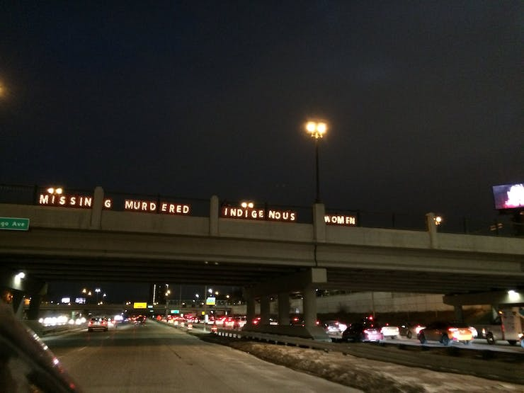 """Activists hold up LED letters that spell out """"MISSING MURDERED INDIGENOUS WOMEN"""" on a highway overpass above Interstate 94 in Minneapolis on February 2, 2018."""