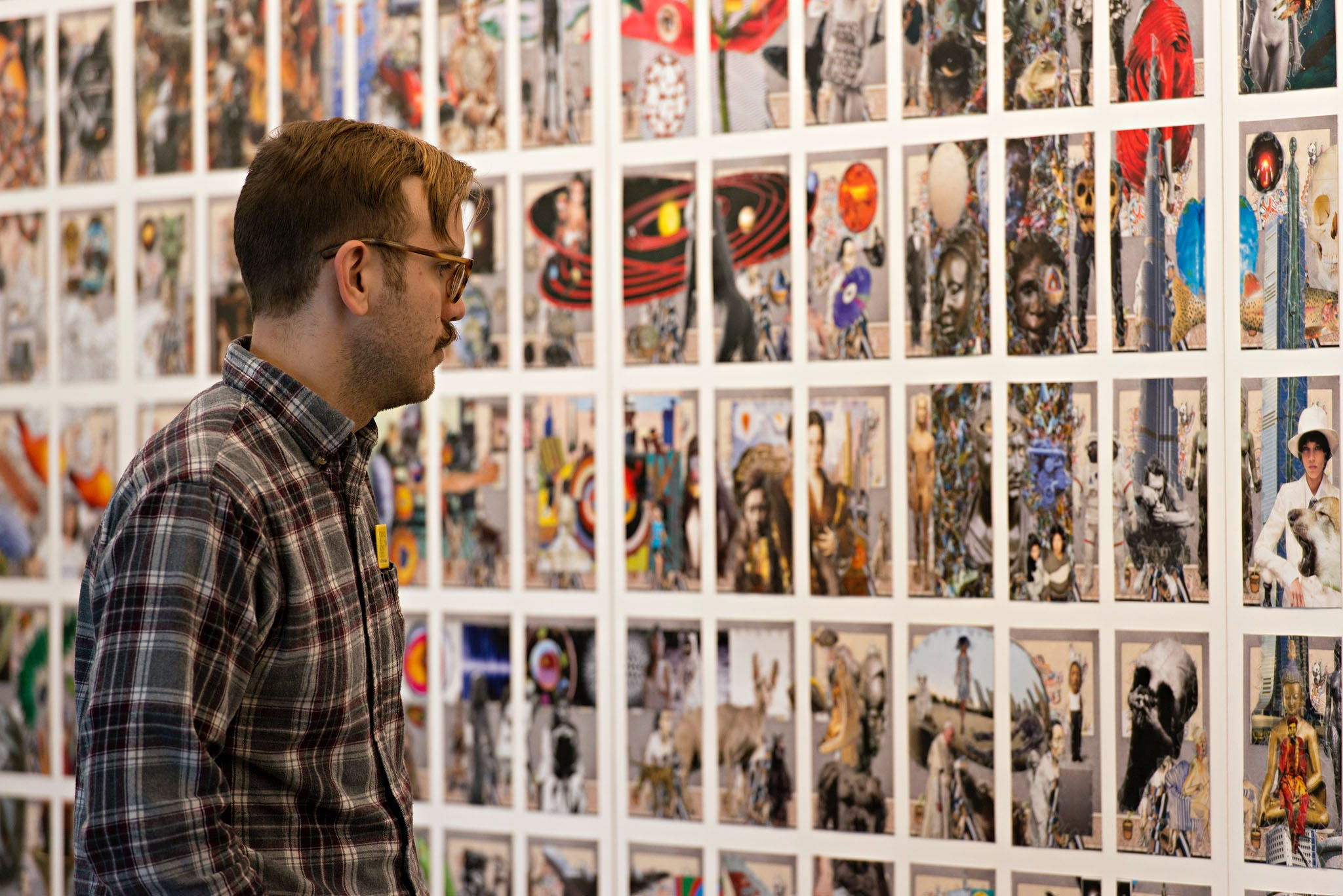 Man in plaid shirt looking at Frank Big Bear collage on wall.