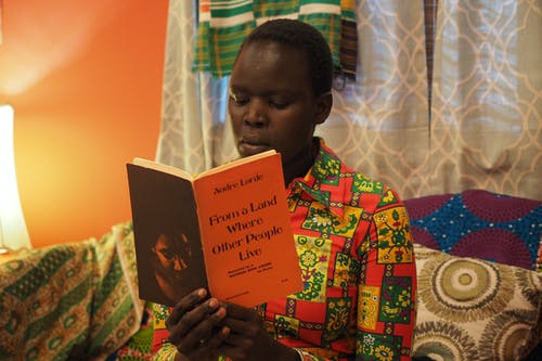 A Black woman wearing a colorful shirt sits on a couch and reads a book by Audre Lorde.