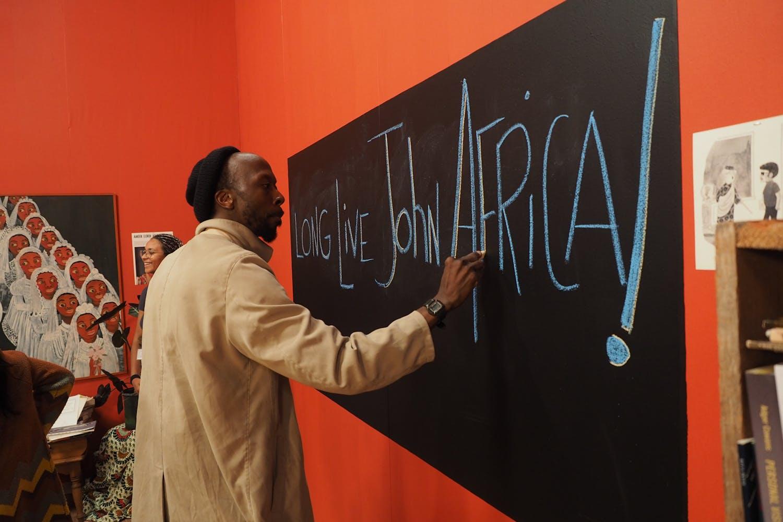 A Black man write on a chalkboard a message that reads Long Live John Africa.
