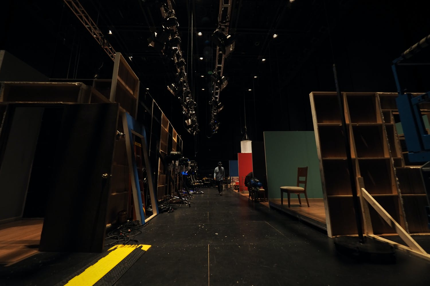 A man walks through the darkened backstage of a theater.