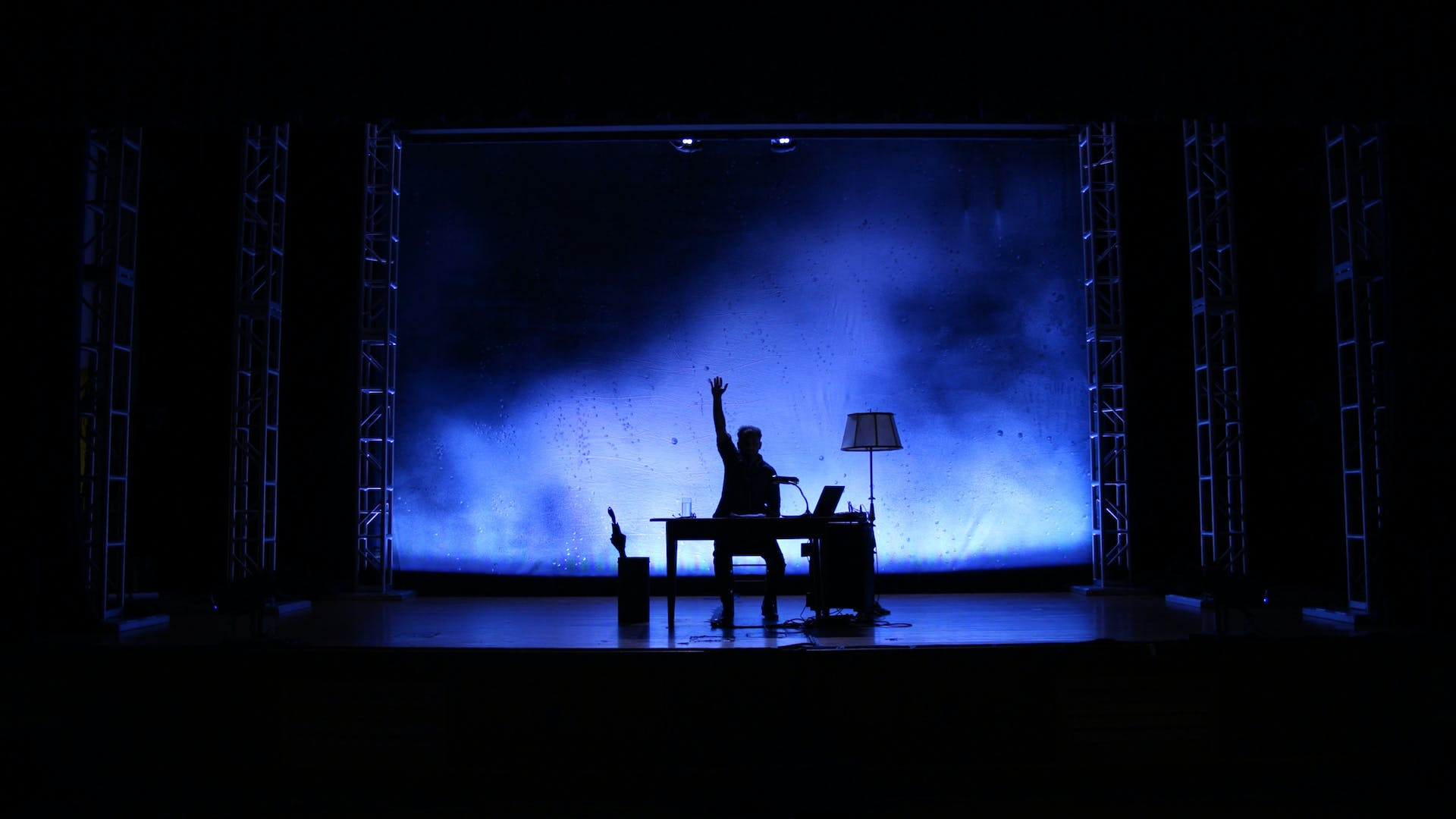 Josh Fox on a stage, in silhouette against a blue background. He is seated at a table with his arm raised in the air.