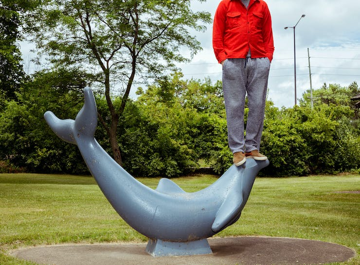 man standing on sculpture of dolphin
