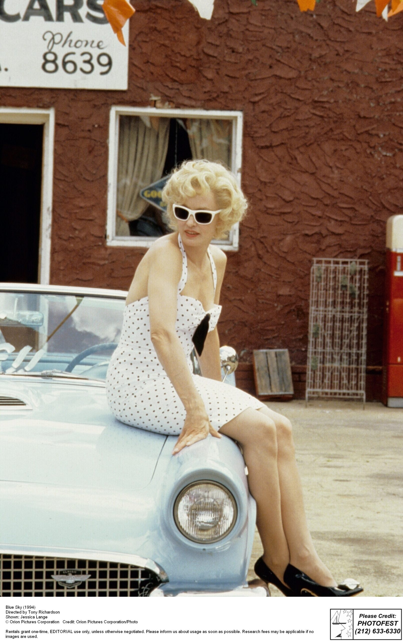 Woman in sunglasses and polka dot dress sitting on hood of a convertible.