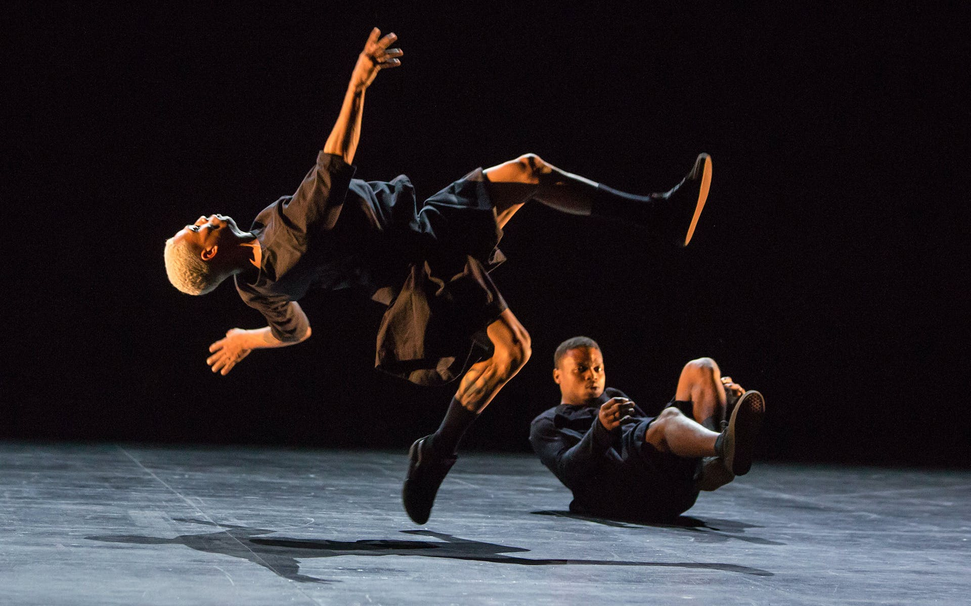 One dancer jumping in mid air and another dancer on the ground.