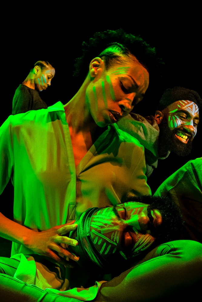 image of dancers superimposed on each other, bathed in colorful light with black background