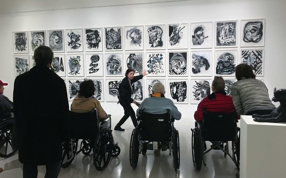 Visitors in wheelchairs listening to tour guide in gallery.