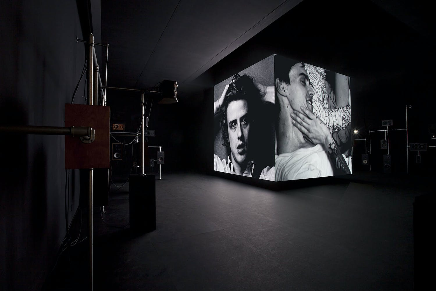 Image of cube structure in gallery with images projected on to the sides
