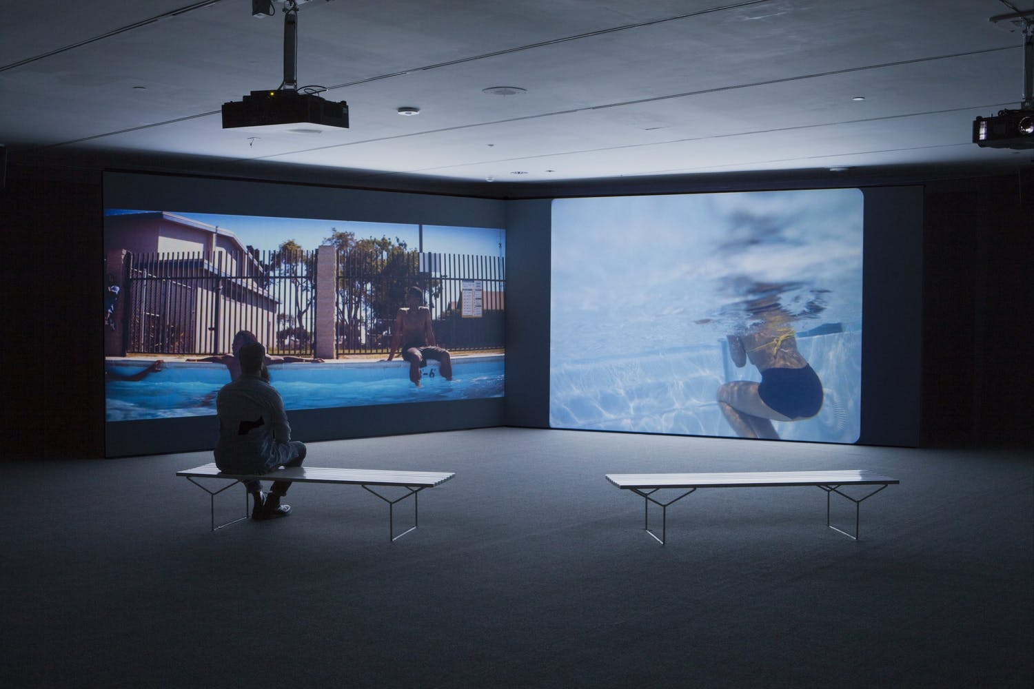Image of gallery with two projections on dark wall and benches and visitor in foreground