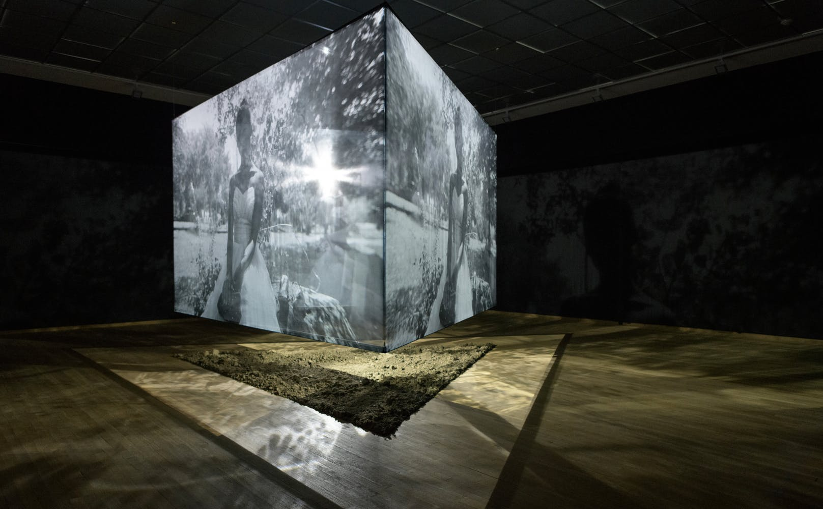 Image of suspended cube within a gallery with images projected on each surface