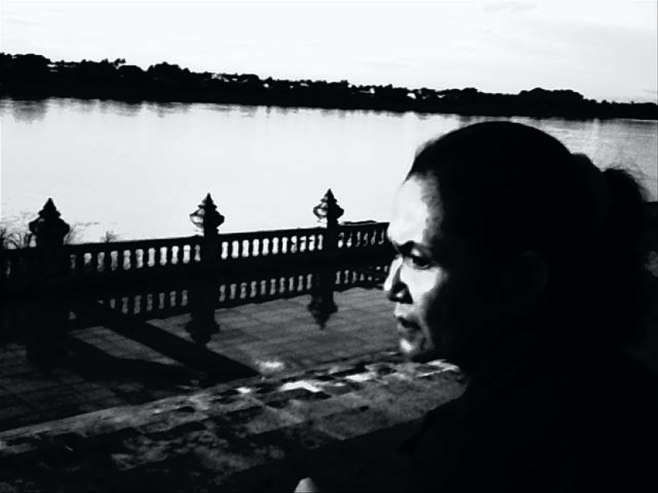 b/w photo of man looking out over river