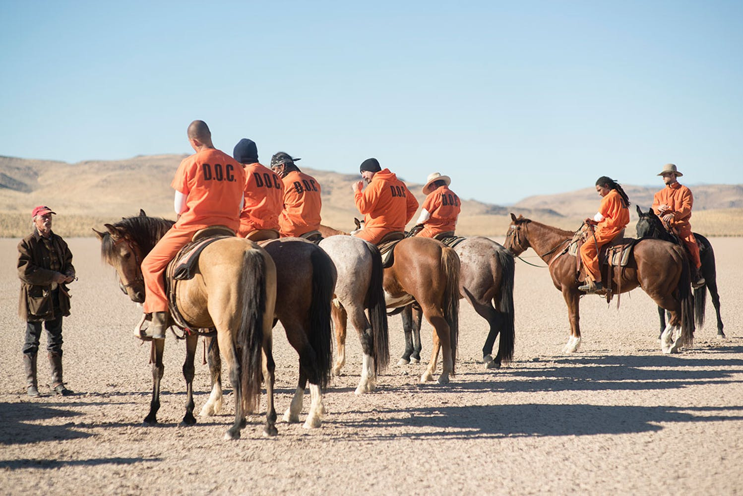 Man in a brown leather coat and red baseball cap talking to seven men in orange D.O.C. jumpsuits sitting horseback.