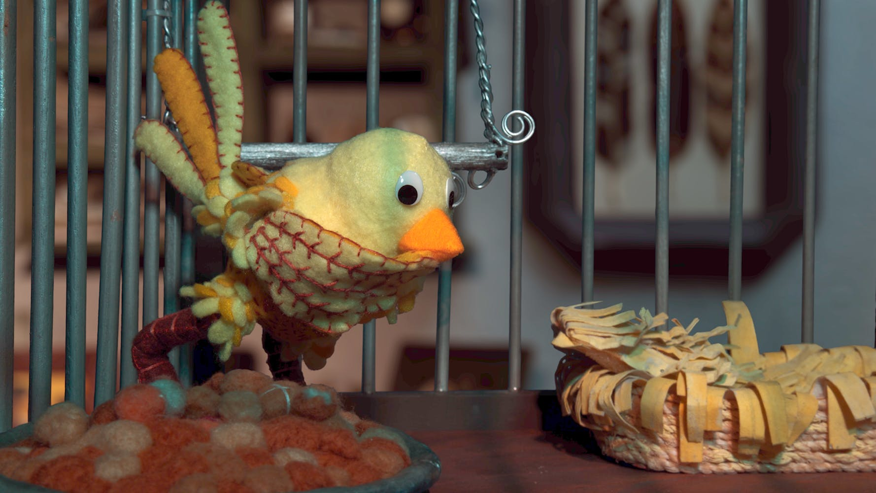 Yellow felt bird in a cage