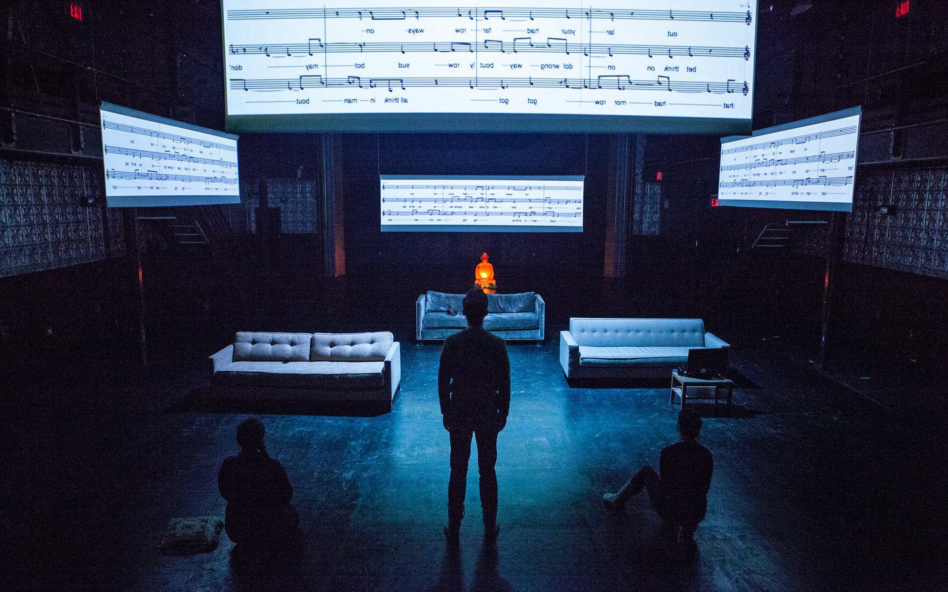 Silhouettes of three people standing and sitting under projections of sheet music.