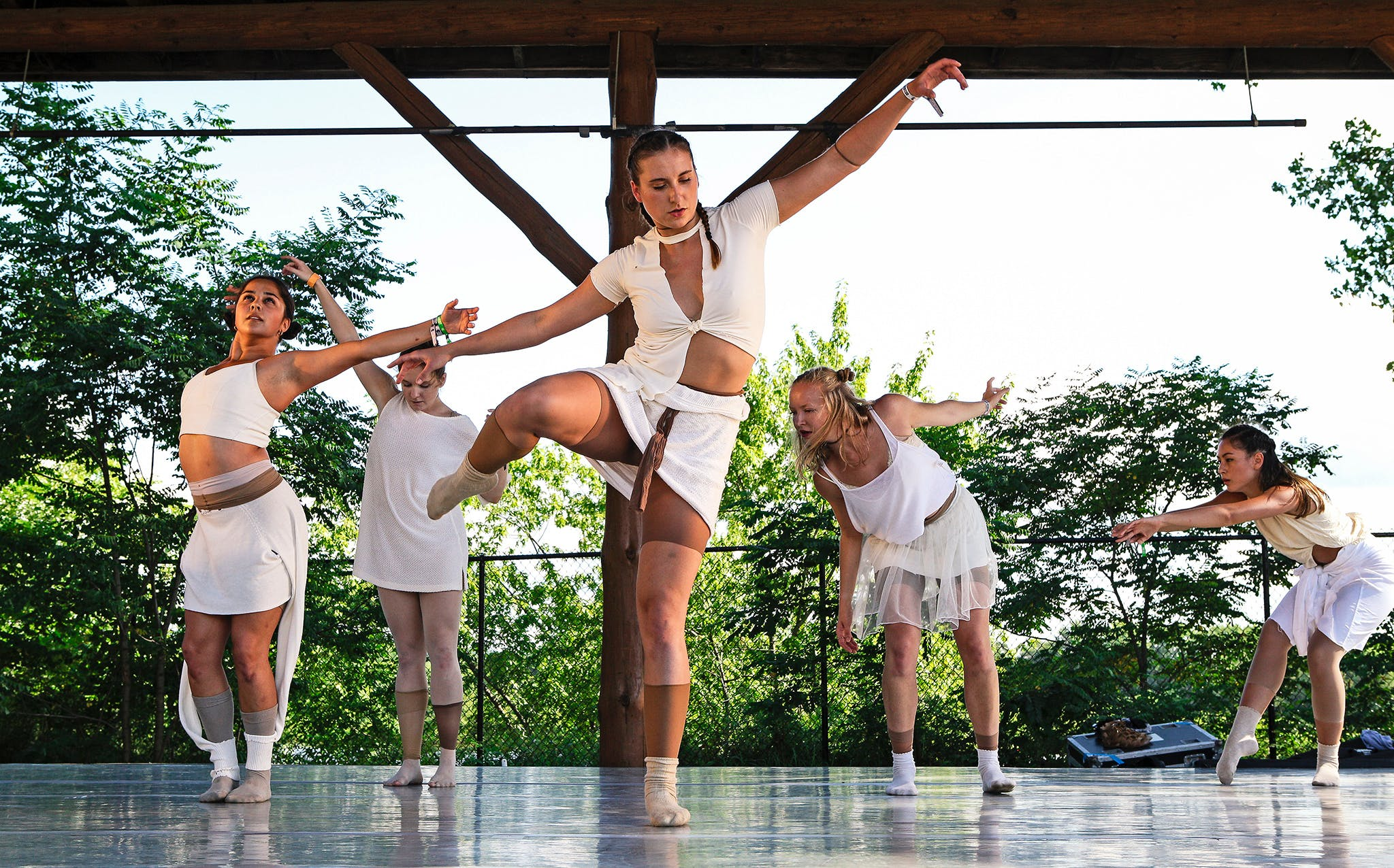 Ladies in white dancing on outdoor stage.