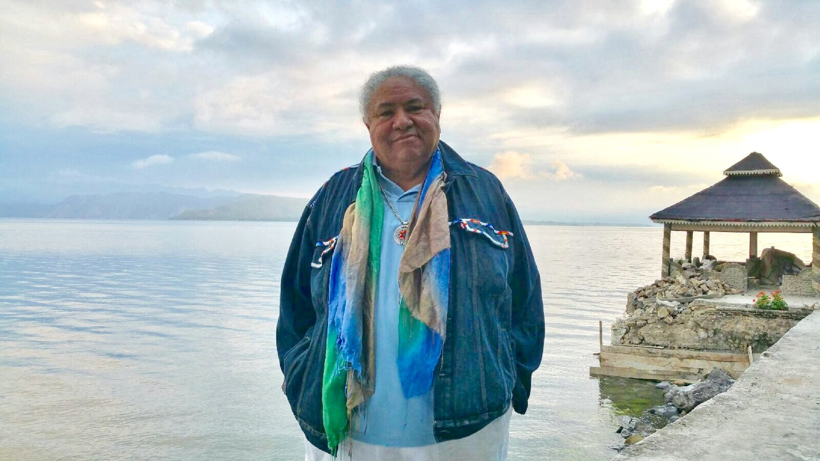 Native man standing in front of a large body of water.