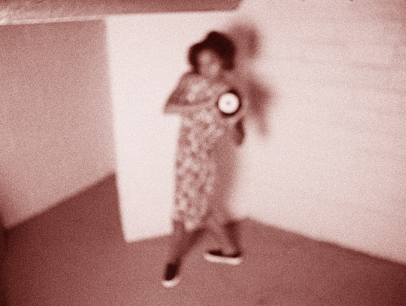 Blurry image of woman in corner holding what appears to be a clock