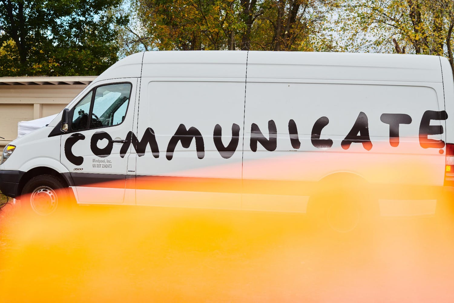 """Image of white van with the word """"Communicate"""" painted on it"""