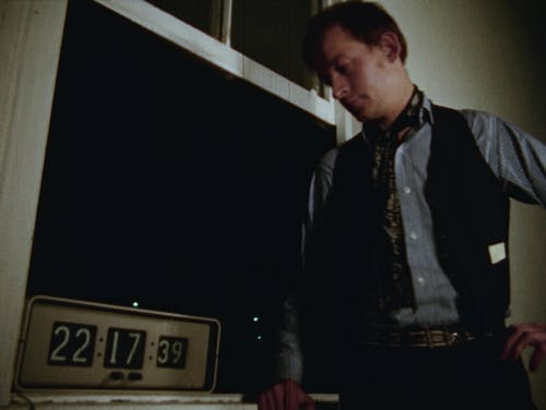 Man wearing a vest and scarf standing near an open window, looking at a clock that says 22:17:39.