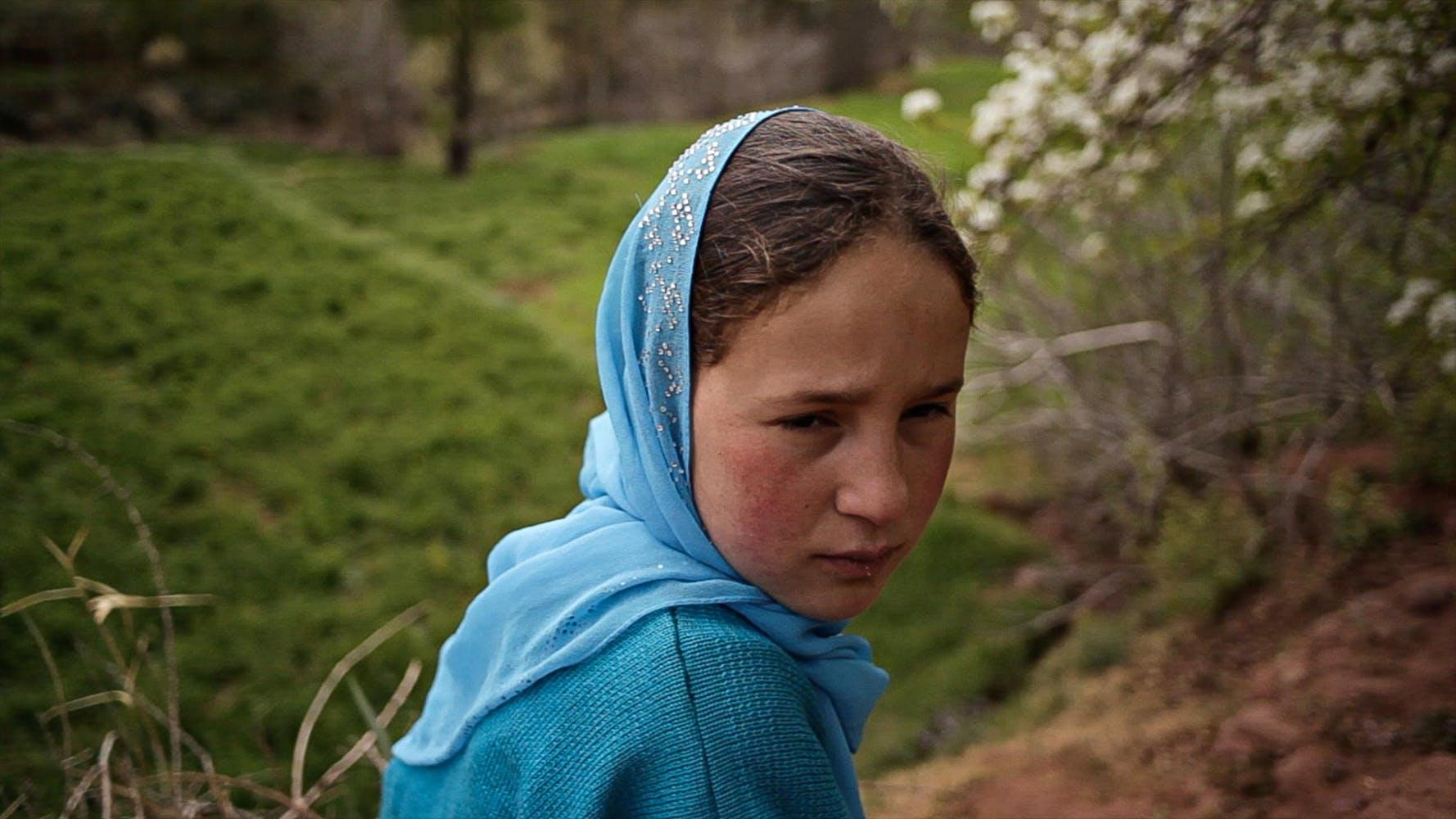 A girl in a blue headscarf sits in a field.