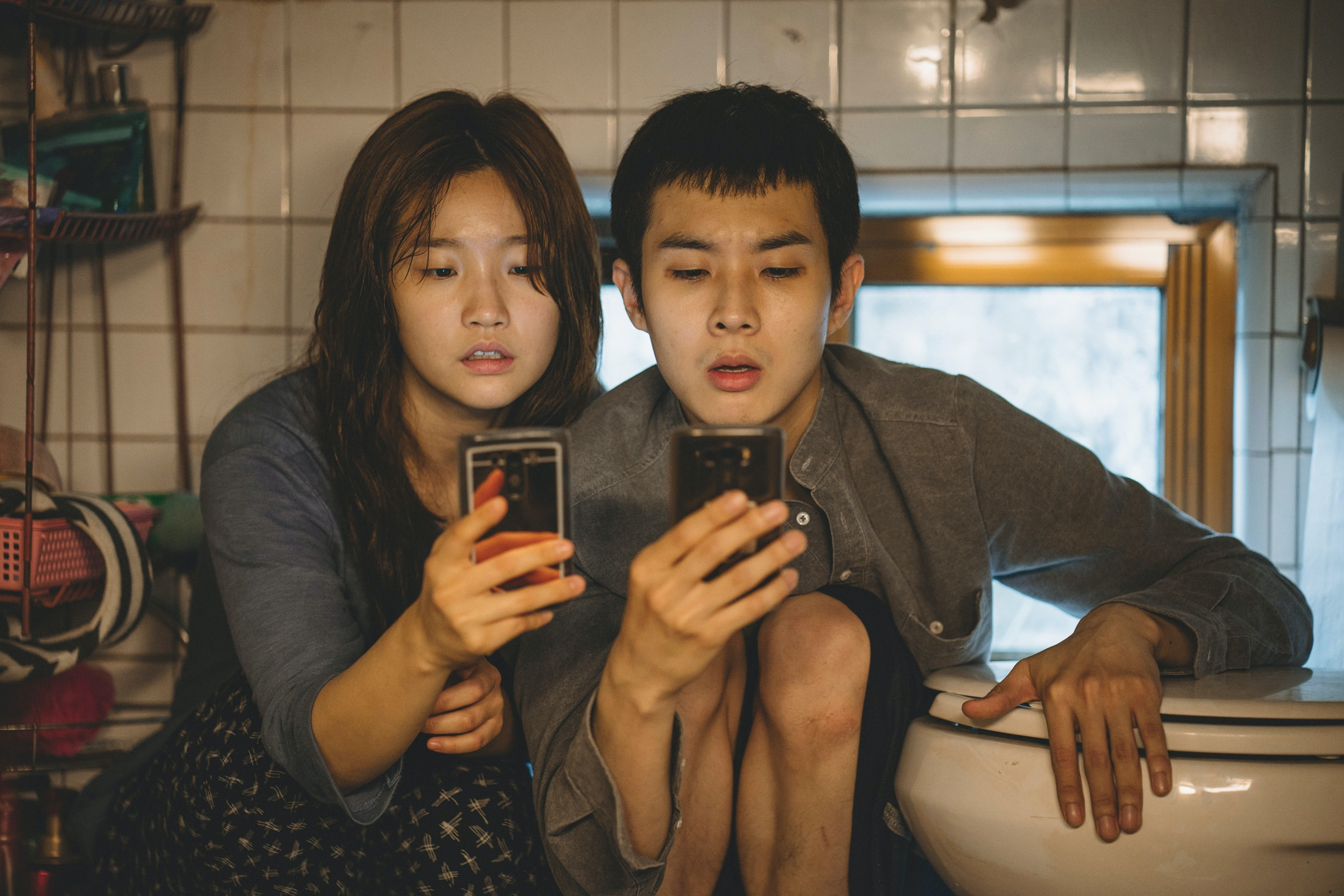 Two young adults in South Korea peering at phones