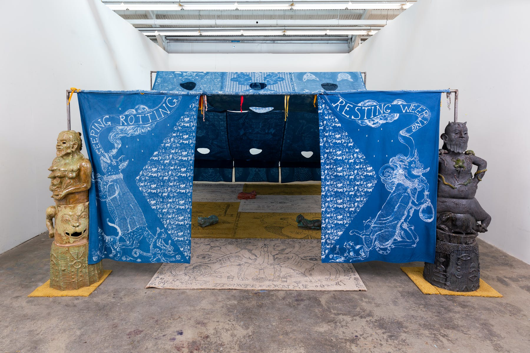 Image of tent made of blue patterned cloth in gallery with statues on either side
