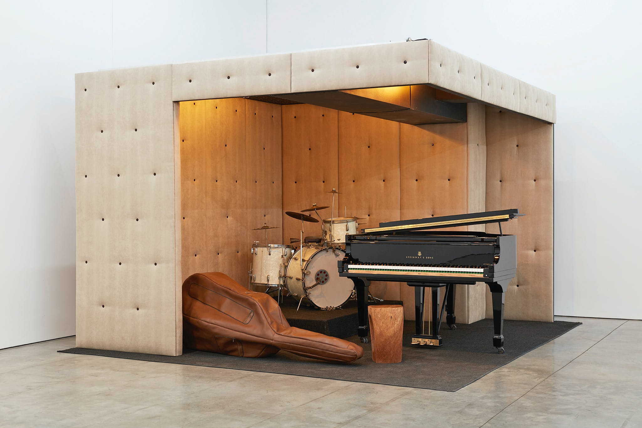 2.5 walls of a padded sound room with instruments inside.