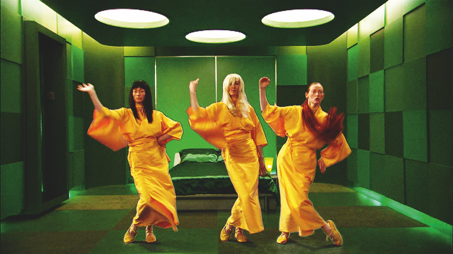 Three women wearing yellow dresses posing in a green room.
