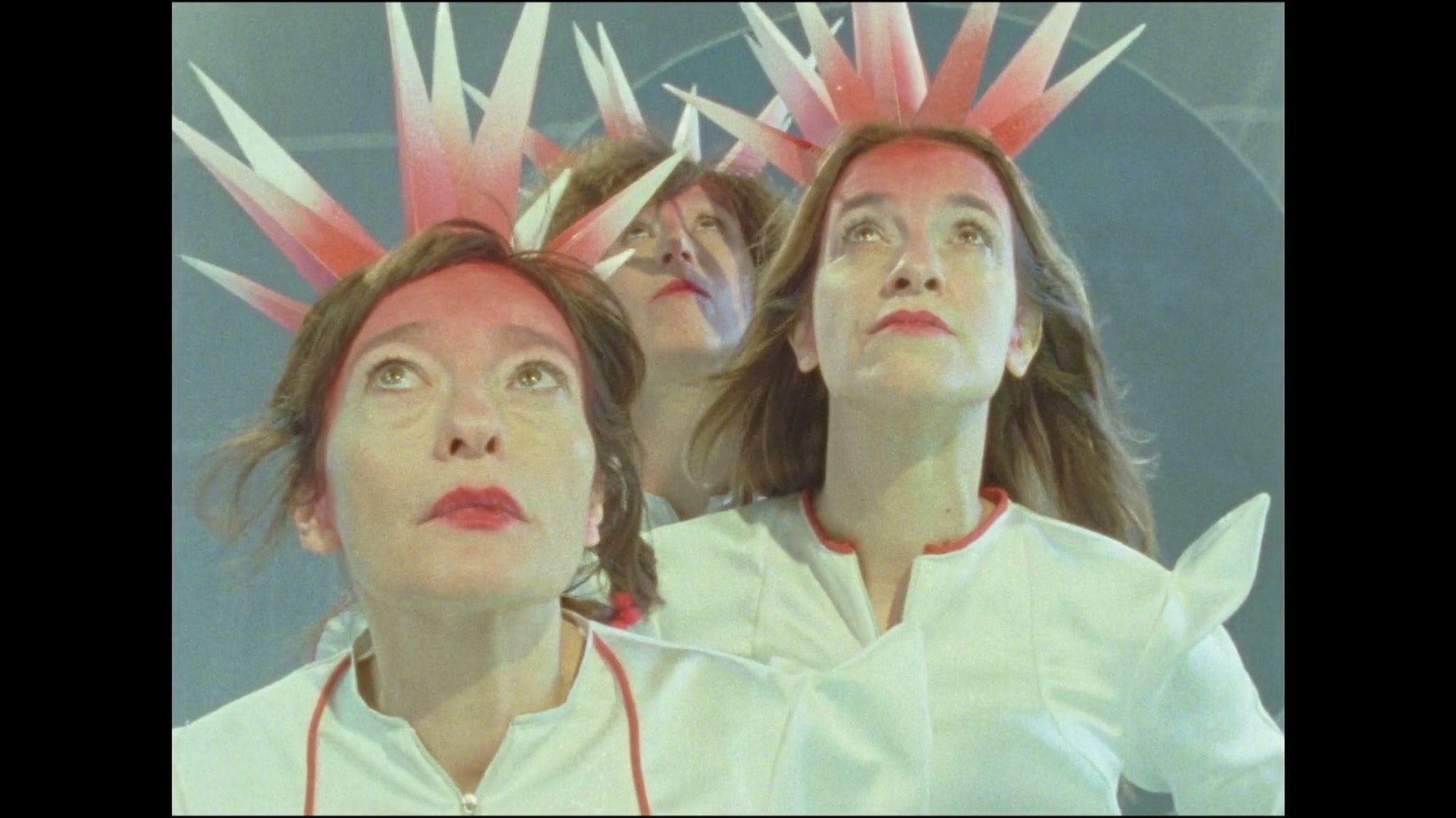 Image of three women looking upward wearing pink and white spiky crowns
