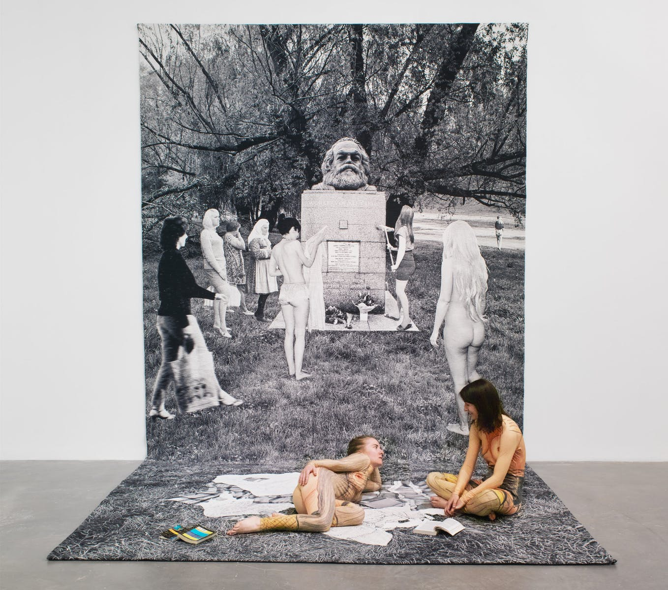 Two women wearing nude jumpsuits sitting on a tapestry that hangs from the wall onto the floor. The tapestry is a black and white image of several women gathered around a gravestone with a sculpture of Karl Marx head on top.