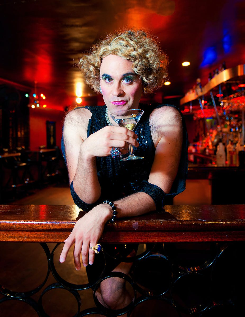 Cross dressed woman in a bar holding drink.