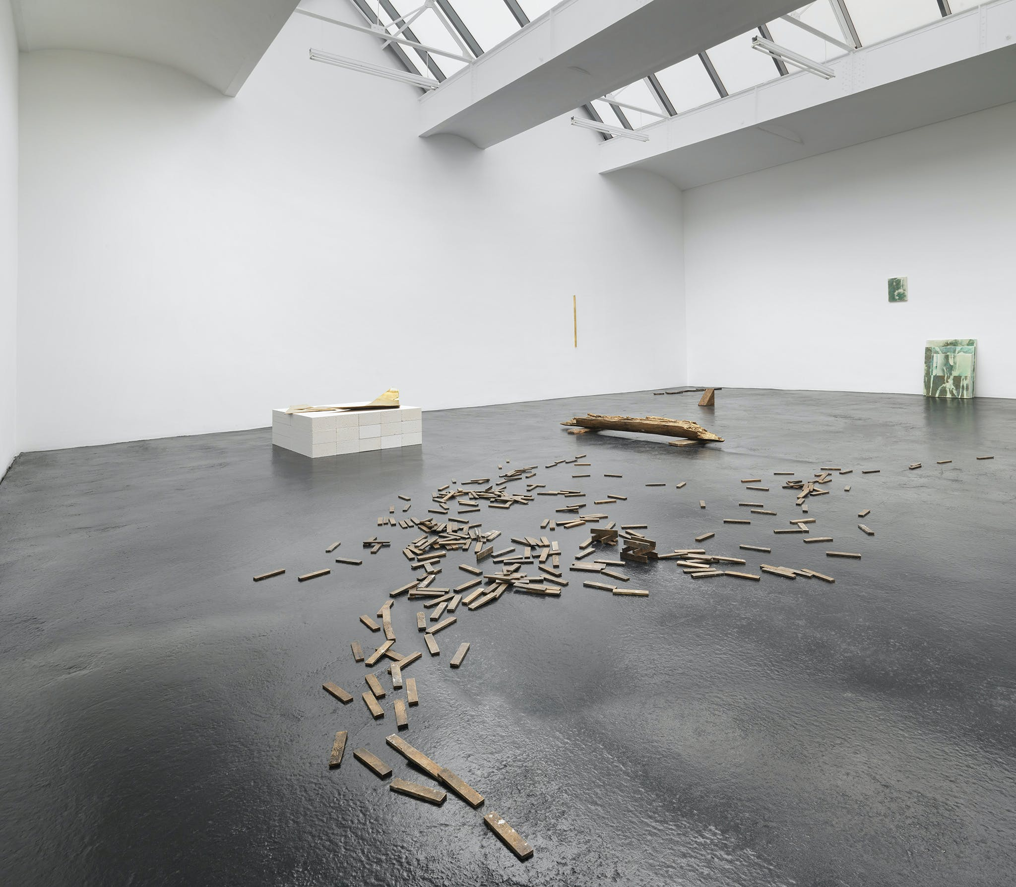 White room, shiny grey floor with wood pieces scattered on the flool and a brick square.