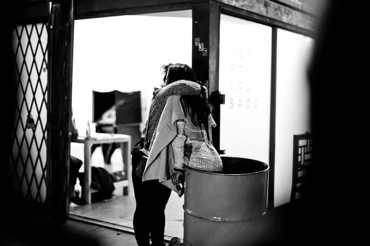 two people hugging while one is in a barrel